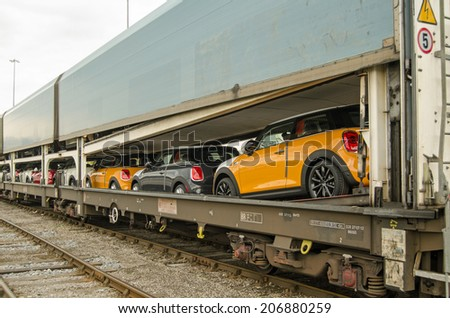 SOUTHAMPTON, UK - MAY 31, 2014: A train full of brand new Mini cars at Southampton about to be exported by ship from the docks.  The Mini car is manufactured at BMW's plant in Cowley, Oxfordshire. - stock photo