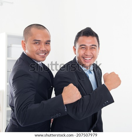 Southeast Asian business men celebrating success in office. - stock photo