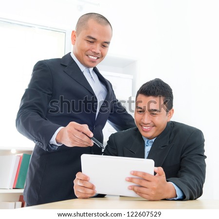 Southeast Asian business people on ebusiness activity, sitting in office. - stock photo