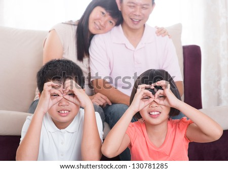 Southeast Asian family having fun at home - stock photo