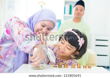 Southeast Asian family saving money at home. Muslim family living lifestyle.