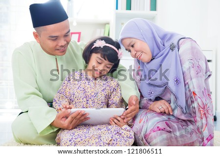 Southeast Asian family using computer internet at home. Muslim family living lifestyle - stock photo