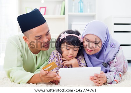 Southeast Asian family using tablet pc computer online shopping with credit card at home. Muslim family living lifestyle. Happy smiling Malay parents and child. - stock photo
