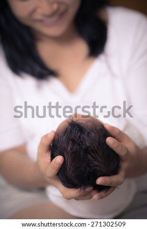Southeast Asian mom happily holds the head of her 10 day old mixed race newborn baby. Shallow focus on dark black hair and mother's fingers. - stock photo