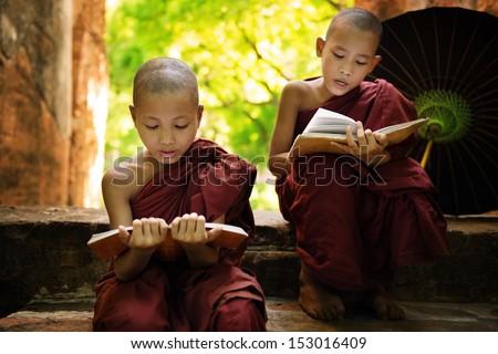 Southeast Asian Myanmar little monk reading book outside monastery, Buddhist teaching. - stock photo