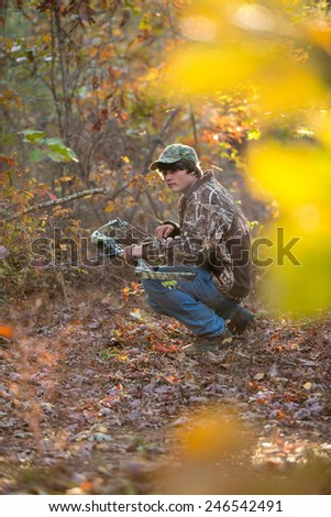 southern american teen boy out in the woods bow hunting for deer - stock photo