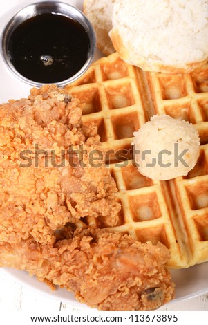 Southern fried chicken and waffles with a country biscuit, honey maple butter and maple syrup - stock photo