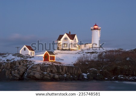Southern Maine's Nubble lighthouse lit at dusk during the holidays. - stock photo