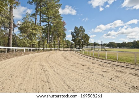 Southern pines and oaks adorn a sandy southern horse racing track and polo field. - stock photo
