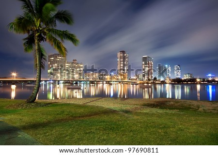 southport at night with palm in foreground (southport, queensland, australia) - stock photo
