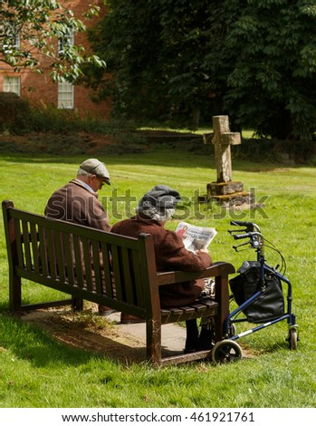 SOUTHWELL, ENGLAND - JULY 31: An elderly couple (man,woman) relaxing on a bench in the graveyard of Southwell Minster. In Southwell, Nottinghamshire, England. On 31st July 2016.