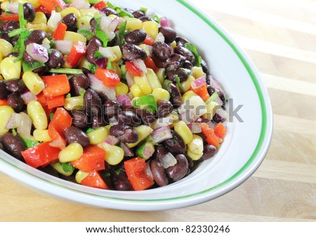 Southwest Black Bean Salad in a bowl sitting on a table. - stock photo