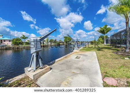 Southwest Florida homes on a canal.  View of canal homes and boat lift on the canal. - stock photo