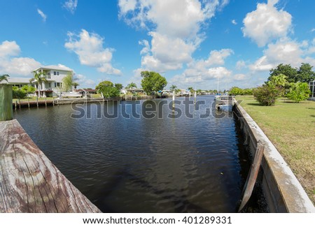Southwest Florida homes on a canal.  View of canal homes from the boat dock along the sea wall of the canal. - stock photo