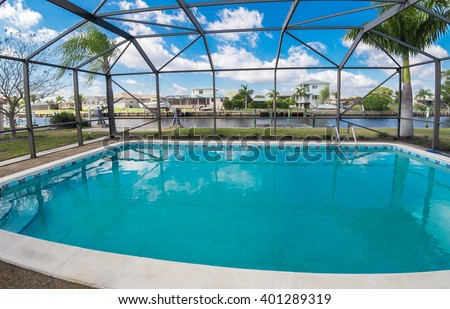 Southwest Florida homes on a canal.  View of canal homes through the screened cage surrounding the pool in one of the homes.