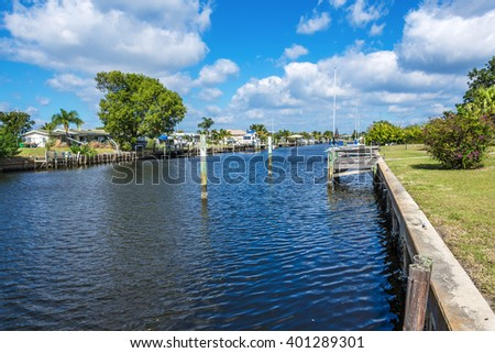Southwest Florida homes on a canal.  View of canal, water, the sea wall and the homes along the saltwater, sailboat canal. - stock photo