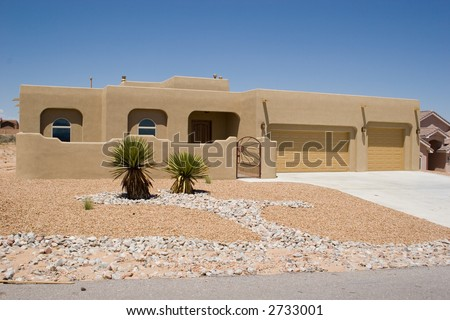 southwestern style house with rock garden landscaping - stock photo
