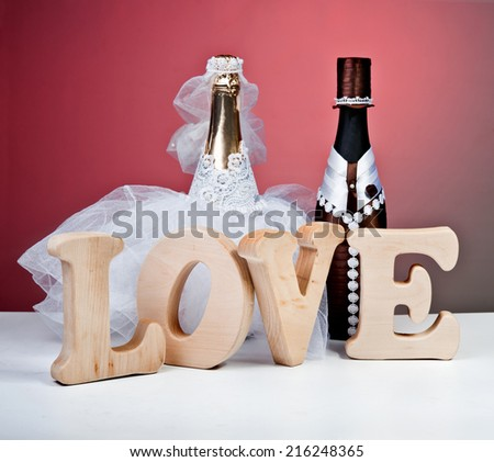 Souvenir bottles for a wedding on a red background.The word love .figurines of the bride and groom.champagne. - stock photo