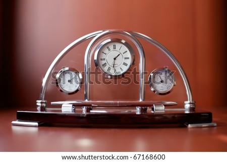 Souvenir clock, thermometer and barometer on a brown table. - stock photo