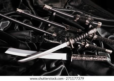 souvenir samurai swords-katana on a black silk - stock photo