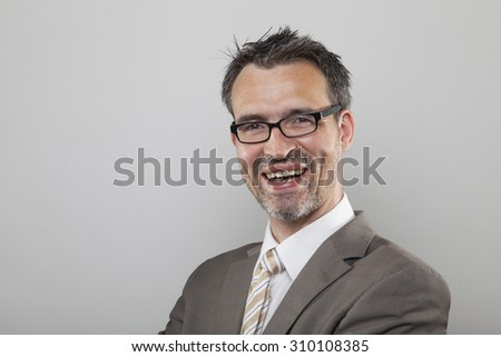 Souvereign winner type business man with designer glasses and stubbly beard laughing smile