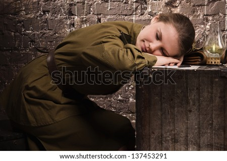 Soviet female soldier in uniform of World War II sleeping in the dugout - stock photo