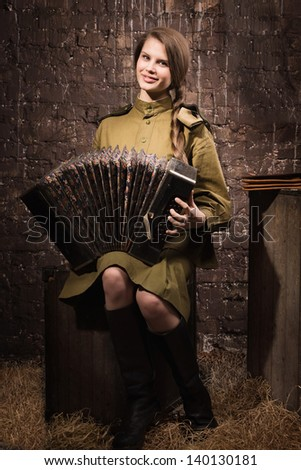 Soviet female soldier in uniform of World War II with an old accordion