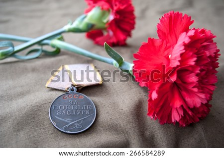 Soviet Medal for Combat Service and two red carnations. Still life dedicated to Victory Day. 9 May. - stock photo