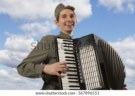 Soviet soldier in uniform of World War II playing the accordion on the blue sky background  - stock photo