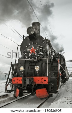 Soviet steam locomotive stands on the platform of the station. - stock photo