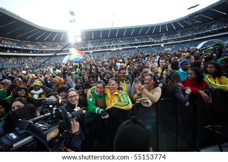 SOWETO - JUNE 10: Fans interviewed for TV while watching international performers at Orlando Stadium for the FIFA World Cup Kick Off Celebration Concert on June 10, 2010 in Soweto. - stock photo
