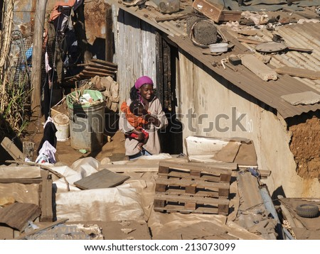 SOWETO, SOUTH AFRICA - AUGUST 15; Woman carries child through the shanty homes in Soweto, South Africa on August 15, 2007. The living conditions of the shanty town can be clearly seen. - stock photo