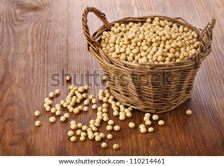Soy beans in a basket on wooden desk - stock photo