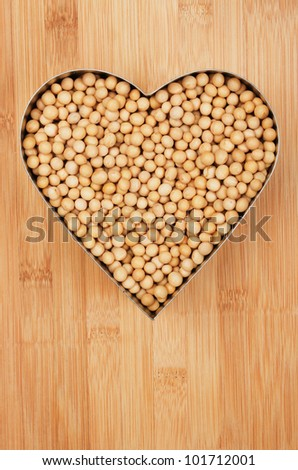 Soy beans in heart shape on wooden background - stock photo