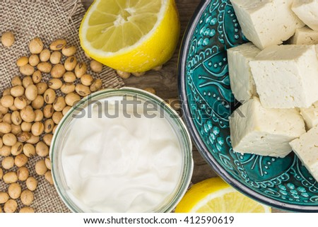 Soy mayonnaise, lemon, soybeans and tofu, on wooden background - stock photo