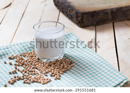 Soy Milk and Seeds on wooden background - stock photo
