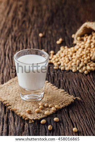 Soy milk and soy bean on wood background