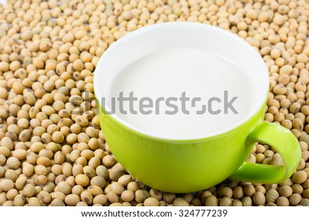 Soy milk in a glass with soy beans on a white background. - stock photo