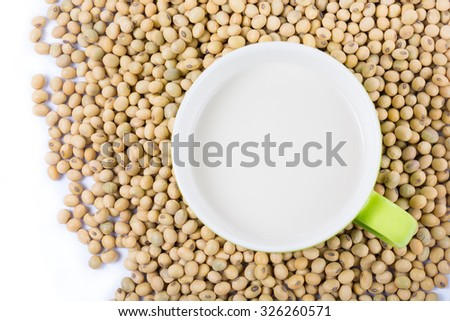 Soy milk in a green cup with soy beans on a white background. Top view. - stock photo