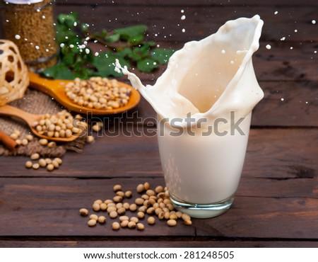 Soy milk splash with beans on wood - stock photo