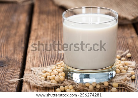 Soy Milk with some Seeds (close-up shot) on wooden background - stock photo