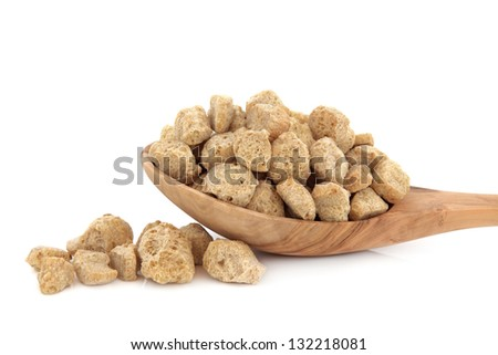 Soy protein chunks in an olive wood spoon over white background. - stock photo