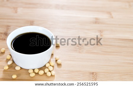 Soy Sauce in a bowl (close-up shot) on bamboo background - stock photo