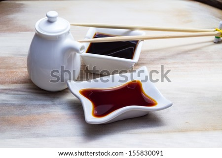 Soy sauce in botle and crockery - stock photo