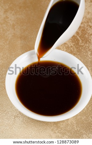 soy sauce poured to a white plate - stock photo