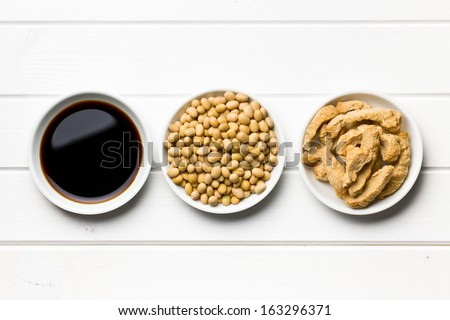 soy sauce, soybeans and soy meat in bowls on wooden table - stock photo