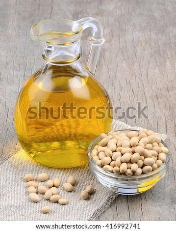 soybean oil with soybean on wooden texture - stock photo