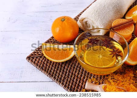 Spa accessories with bowl of bowl of essential oil on wicker mat, on color wooden background - stock photo