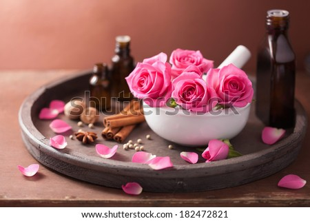 spa and aromatherapy set with rose flowers mortar and spices  - stock photo