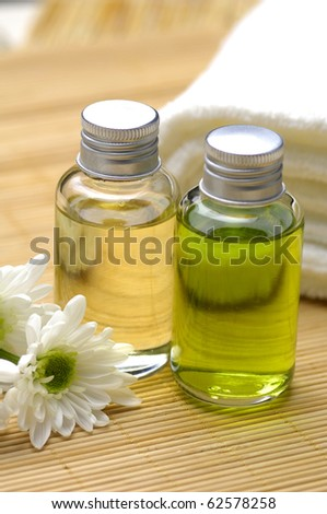Spa and beauty treatment -bottles with essential oils and towel on bamboo stick straw mat - stock photo